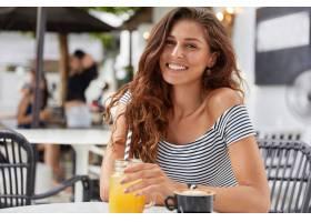 可爱的年轻女性留着深色的长发在咖啡厅_955013901