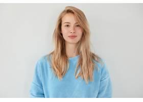 可爱的金发女人表情严肃穿着蓝色毛衣皮_1054509701