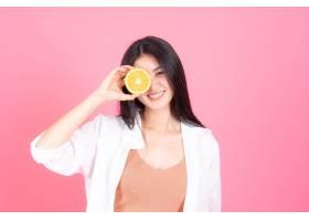 美女亚裔可爱女孩在粉色底色上捧着橙子健康_455057401
