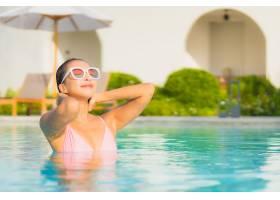 肖像美丽的亚洲年轻女子在海边的室外游泳池_1191552801