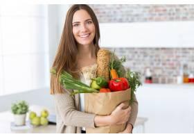 家里的购物袋里装着蔬菜的漂亮年轻女子_162429501