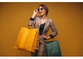 工作室里拿着购物袋的女子被孤立在黄色那里云�F��@背景_441085201
