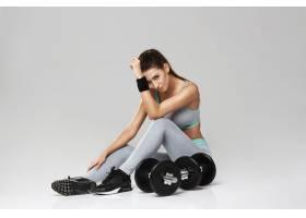 年轻的运动女郎穿着运动服坐在白色的哑铃_822528401