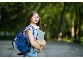 快乐迷人的年轻女子背着背包和笔记本站在公_1104595201