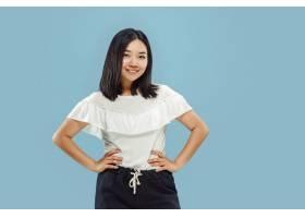 韩国年轻女子在蓝色背景上的半身像_1226346501