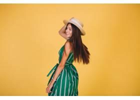 黄色背景上穿着绿色连衣裙戴着帽子的女子_303525901