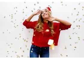 戴着圣诞老人化妆礼帽的庆祝女孩在白色墙上_1099027001