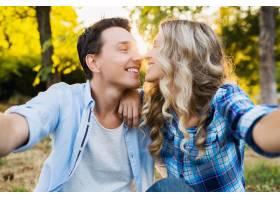 亲吻坐在公园里的年轻时尚情侣男女幸福家_969952501