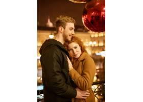 在节日的灯光下一对幸福的情侣在傍晚的街_960403901