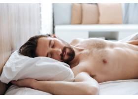 迷人的留着胡须的年轻人睡在床上_819656701