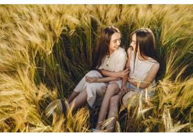 田野里两个穿着白色连衣裙留着长发的姐妹_965884501