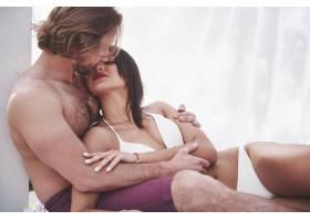 美丽性感的情侣男女在海滩上穿着泳衣浪漫_1000208501
