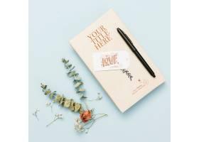 用钢笔和鲜花制作书本样机的俯视图_85733550102