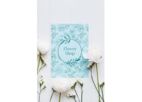 蓝色的花店样机和白色的花朵_77400710102