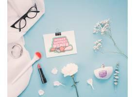 蓝色背景上有鲜花和化妆的纸板样机_69663790102