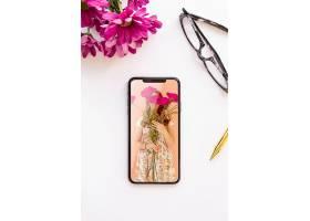 靠近鲜花和眼镜的手机样机_89038430102
