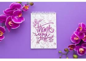 紫色背景上的笔记本和花朵的俯视图_55760840102
