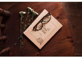 带鲜花和眼镜的椅子上的书俯瞰_85734380102
