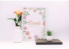 带有花卉装饰和框架样机的书桌构图_89696810102