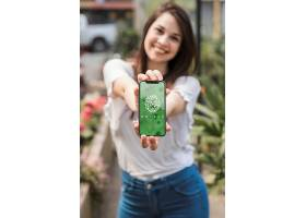 拿着带有园艺概念的智能手机样机的女孩_36567690102