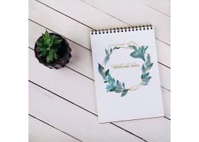 顶视图中带有装饰性植物的春季笔记本样机_41368580102