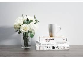 装有鲜花马克杯和堆放书籍的花瓶_82445390102