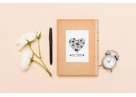 摆着钟表和玫瑰花的平铺着的书_85733910102