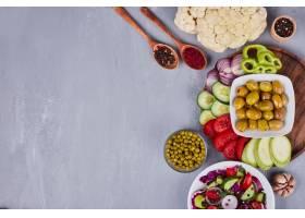 蔬菜沙拉周围有切片和切碎的食物和其他小_1094471501