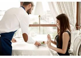 餐厅里英俊的服务员正在为一位年轻女士提供_644980901