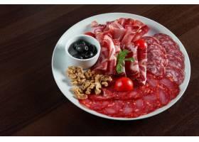 餐桌上有各种意大利腊肠肉盘配以黑橄榄和_943704701