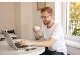 留着胡子的年轻英俊男子坐在咖啡馆的餐桌旁_1110298101