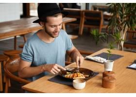留着胡子的英俊青年用刀叉吃着好吃的东西时_953302401