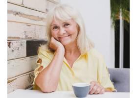 老年妇女坐在厨房里戴着杯子微笑_516223401
