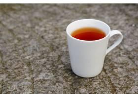 背景模糊的灯光下放在地上的白色杯子里的茶_985221201