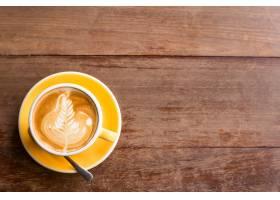 热艺术拿铁咖啡放在木桌上的杯子里_120364301