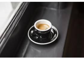 窗台上黑色杯子里的剩饭咖啡_310062701