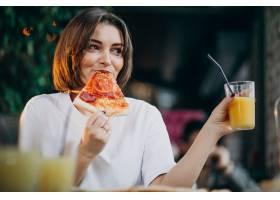 年轻漂亮的女人在酒吧吃披萨_664023501