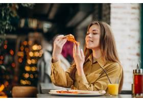 年轻漂亮的女人在酒吧吃披萨_664023701