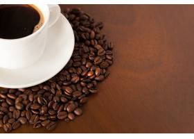 木桌上咖啡杯和咖啡豆的局部视图_132355601