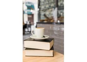 木桌上的书上放着一杯咖啡_305339601