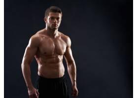 肌肉健美的年轻运动员在黑色背景上赤裸上身_8990557