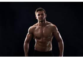 肌肉健美的年轻运动员在黑色背景上赤裸上身_8990588