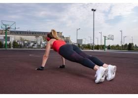 穿着弹力服的运动女性在陆地上做热身活动_5542850