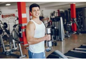 一个年轻健壮的男孩在体育馆里从事体育活动_2533988