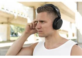 侧身运动的男子一边听音乐一边看向别处_9156717