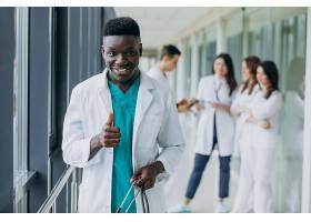 一名非裔美国医生竖起大拇指站在医院的走_7869371