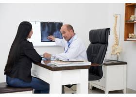 医生侧视图指向脊柱弯曲X光片向女性患者解_5698318