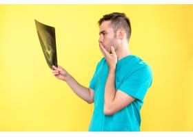 男医生手持X光片在黄墙上的正面图_12351692