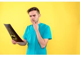 男医生手持X光片在黄墙上的正面图_12351693