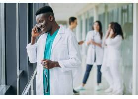 一名非洲裔美国医生站在医院的走廊里打电话_7869374
